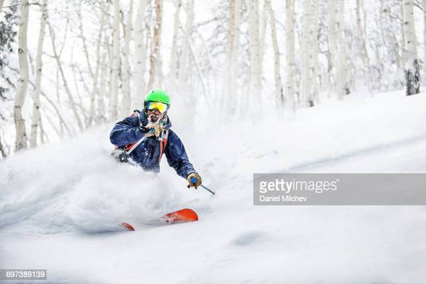 Skier making powder turn in deep snow.