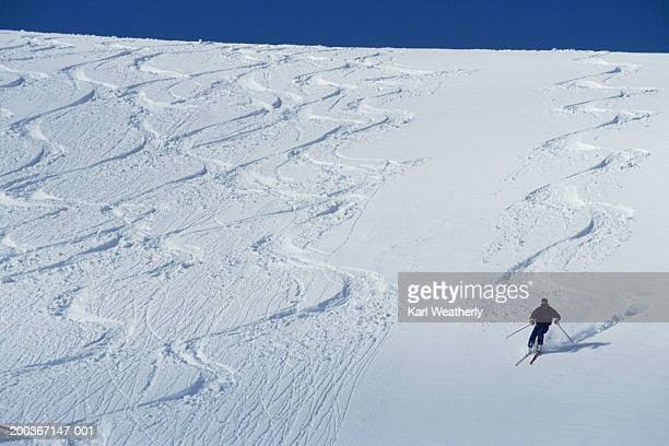 skier making tracks, other tracks visible, elevated view - alpine skiing stock pictures, royalty-free photos & images