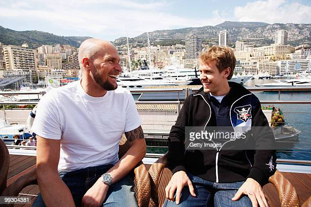 Skier Marco Buechel and Sebastian Vettel of Germany and Red Bull Racing are seen on the Red Bull Energy Station during previews to the Monaco Formula...