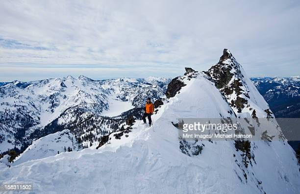 a skier on a ridgeline, pausing before skiing the slot on snoqualmie peak in the cascades ranges, washington state, usa. - snowfield stock pictures, royalty-free photos & images