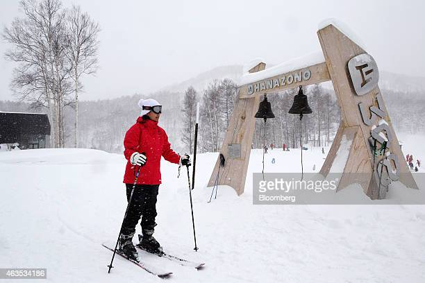 A skier passes bells displayed in the base area of the Niseko Hanazono resort operated by Nihon Harmony Resorts KK in Kutchan Hokkaido Japan on...