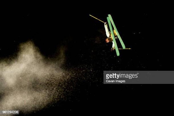 skier performing stunt against sky at night - freestyle skiing stock pictures, royalty-free photos & images
