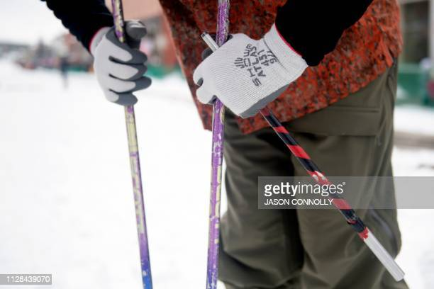 A skier rest against his poles while holding a baton in his hand before competing in the 71st annual Leadville Ski Joring weekend competition on...