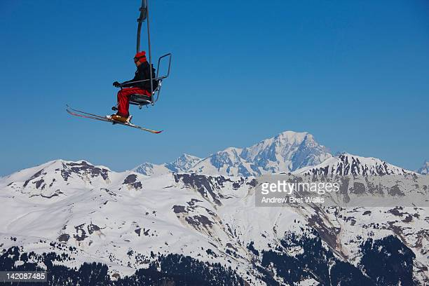 skier riding a mountain chairlift - courchevel stock pictures, royalty-free photos & images