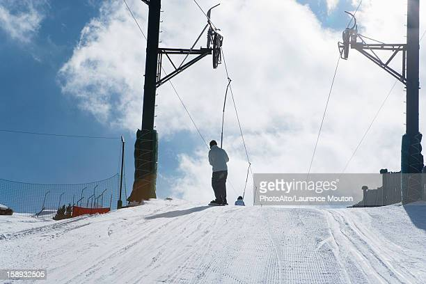 Skier riding ski lift, rear view