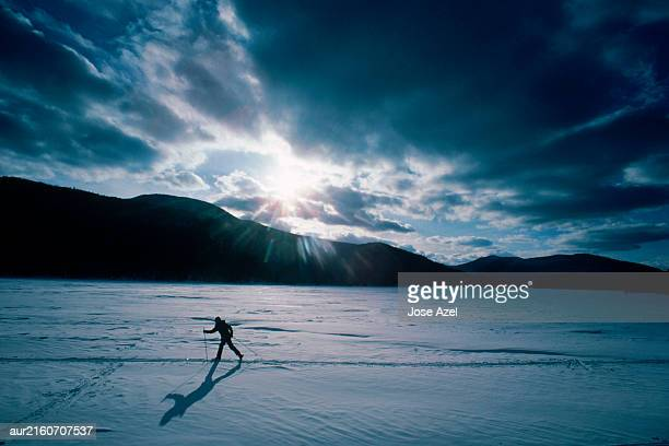 A skier skies along white, snowy land under a cloudy sky, Maine, USA.