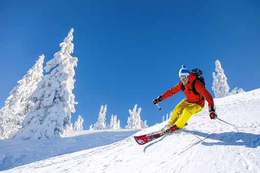 Skier skiing downhill in high mountains against blue sky 857763588
