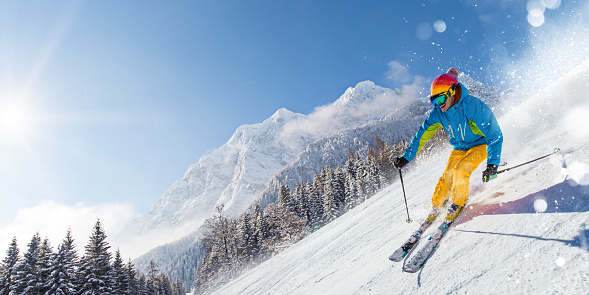 Skier skiing downhill in high mountains 1056356200