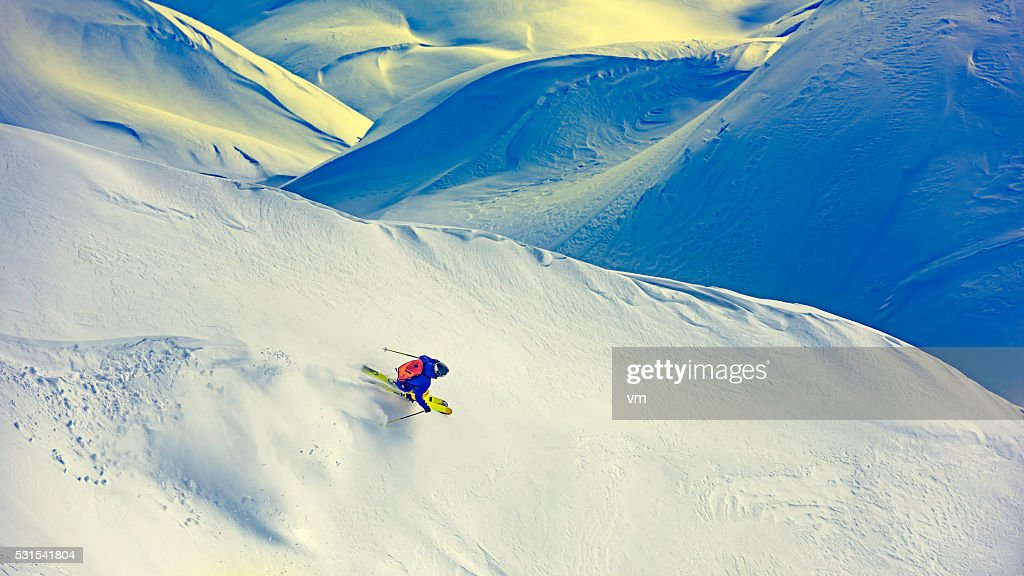 Top view of a free skier descending down a snowcapped hill.
