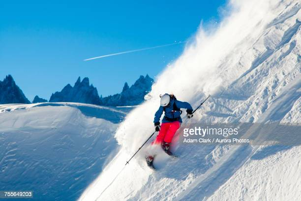 Skier skiing through fresh powder down steep mountainside, Chamonix, France