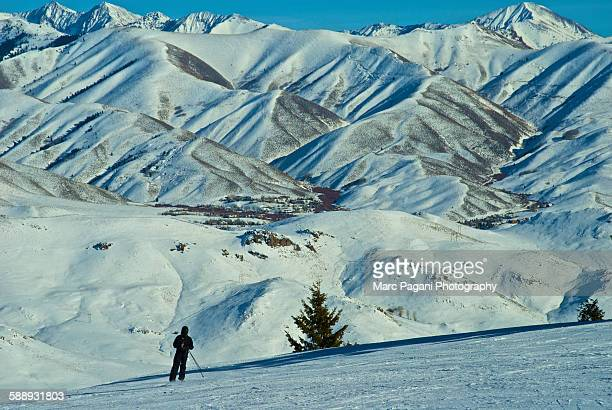 a skier skis in the sawtooth mountain range - ketchum idaho stock photos and pictures