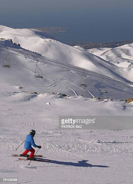 A skier slides down the slopes overlooking Beirut and the Mediterranean sea on a sunny day 18 January 2008 at the Faraya ski resort in the mountains...