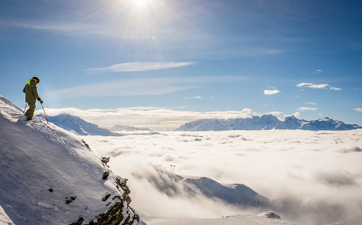 Skier standing on a rock above the clouds 934059036