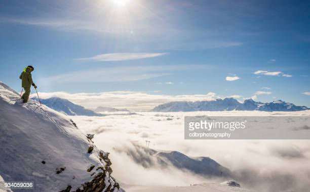 skier standing on a rock above the clouds - mountain peak stock pictures, royalty-free photos & images