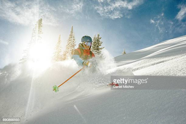 skier takig a turn in deep powder on a sunny day. - deep snow stock pictures, royalty-free photos & images