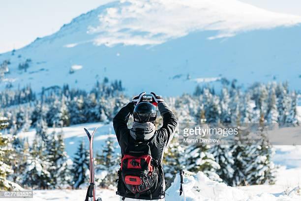 Skier taking photo of the snowy mountain