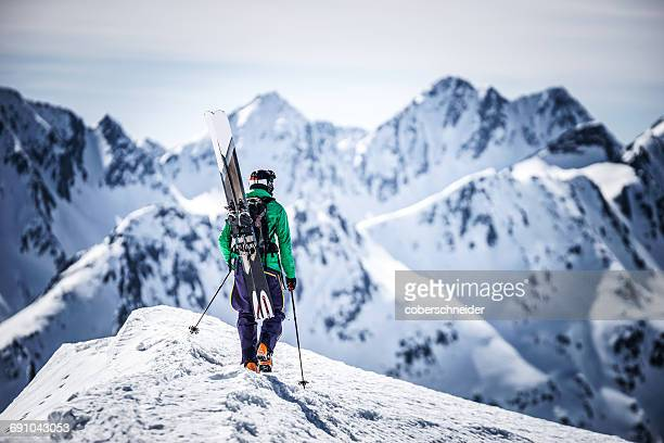 skier walking along ridge carrying his skis, andermatt, uri, switzerland - wintersport stock-fotos und bilder