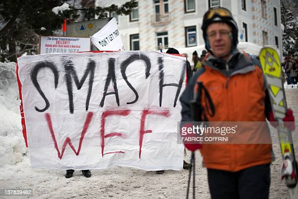 A skier walks past members of 'Occupy WEF' holding a banner during a demonstration on January 28 against the World Economic Forum annual meeting on...