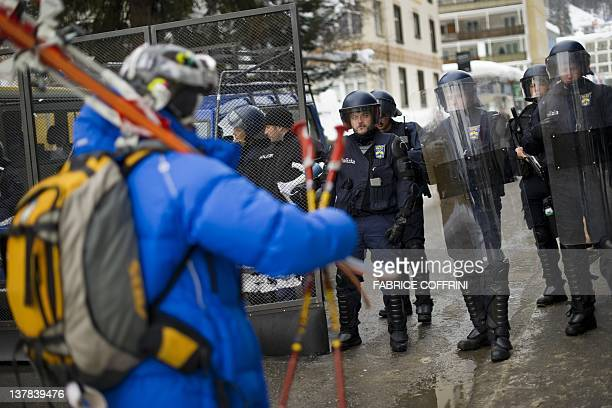 A skier walks past Swiss riot police officers during a demonstration on January 28 against the World Economic Forum annual meeting on January 28 2012...