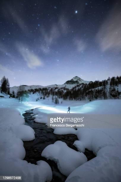 skier with front lamp explore mountains at night. italian alps - italia ストックフォトと画像