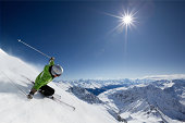 Skier with sun and mountains