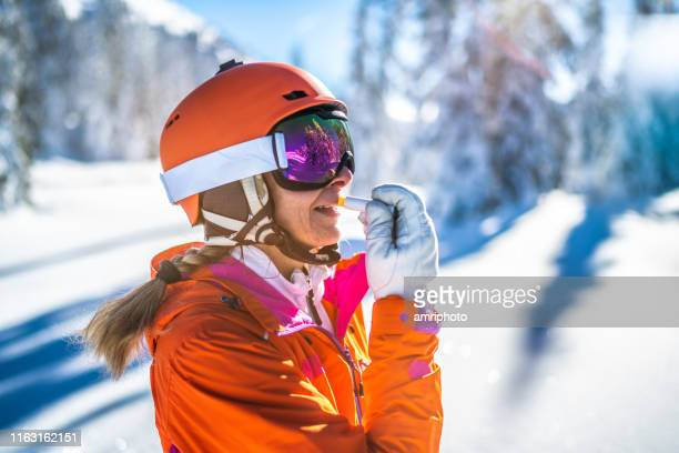 skier woman with skiing helmet putting on sunscreen lip protection - lip balm stock pictures, royalty-free photos & images