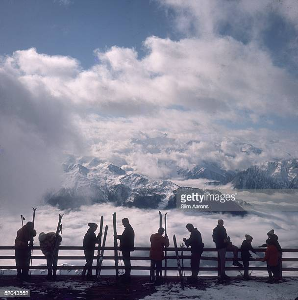 Skiers admire the view across a valley of clouds at Verbier 1964