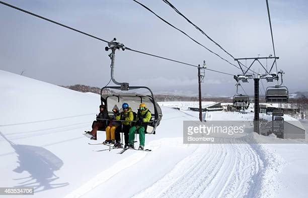 Skiers and a snowboarder left ride on a lift at the Niseko Hanazono resort operated by Nihon Harmony Resorts KK in Kutchan Hokkaido Japan on Sunday...