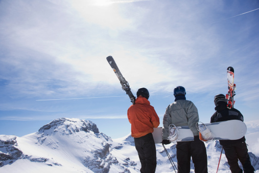 Skiers and a snowboarder on a mountain carrying their equipment - gettyimageskorea