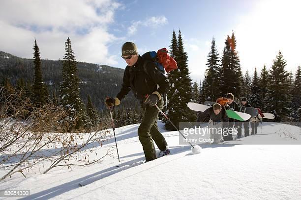 skiers and snowboarders climb uphill - wasserform stock-fotos und bilder