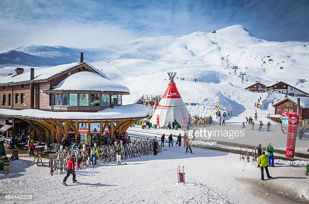 skiers at alpine ski resort high on snowy mountain switzerland - apres ski stock pictures, royalty-free photos & images