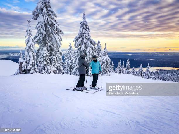 skiers at top of ski run, sunset view of city - vancouver canada stock pictures, royalty-free photos & images