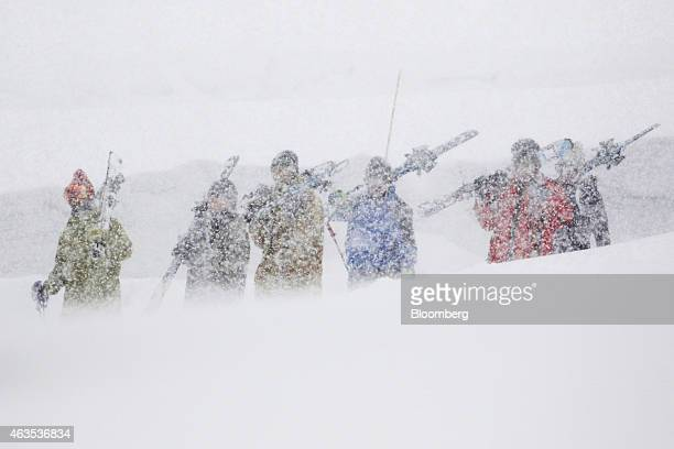 Skiers carrying skis walk on a slope at the Grand Hirafu resort operated by Tokyu Resort Service Co in Kutchan Hokkaido Japan on Saturday Feb 14 2015...