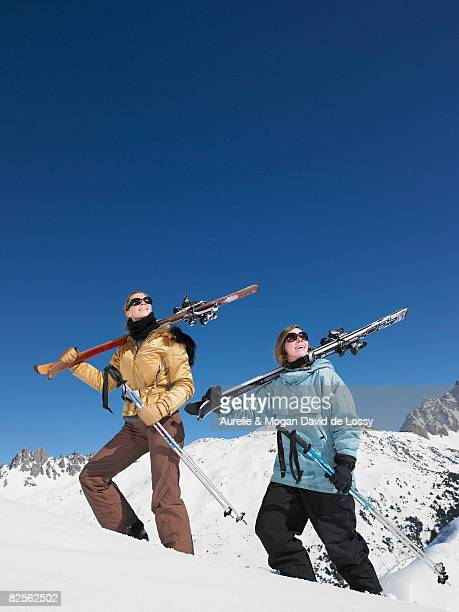skiers climbing mountain admiring view - meribel stock photos and pictures