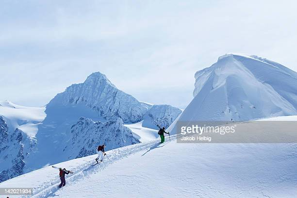 Skiers climbing snowy slope