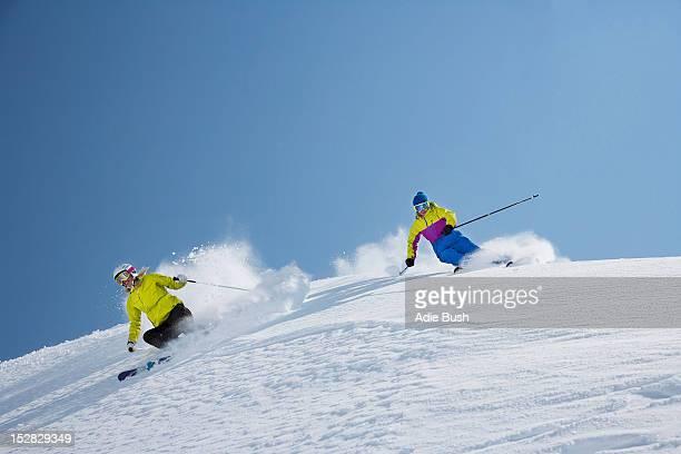 Skiers coasting on snowy slope