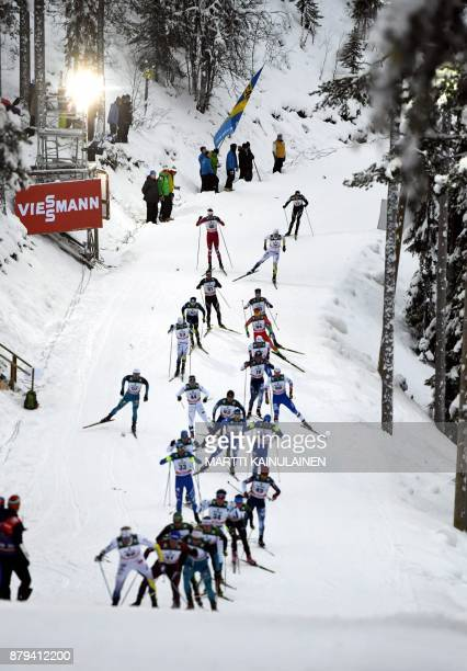 Skiers compete during the Mens' cross country skiing 15km free style pursuit event at the FIS World Cup Ruka Nordic 2017 in Ruka Kuusamo in northern...