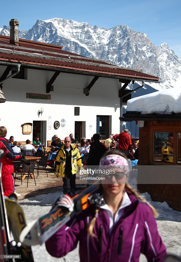 Skiers enjoying the sun at the terrace of the ski hut restaurant Brettlalm and the panoramic view of the mountain Zugspitze on March 19, 2010 in Lermoos, Tyrol, Austria. Zugspitze has got an altitude of 2962 meters and is the highest mountain and only glacier of Germany.