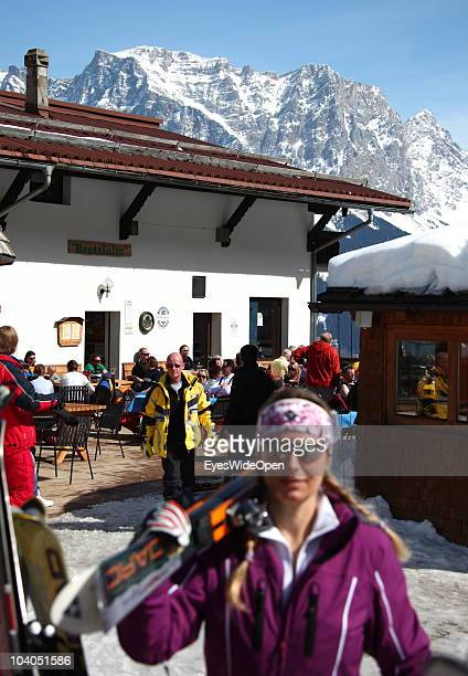Skiers enjoying the sun at the terrace of the ski hut restaurant Brettlalm and the panoramic view of the mountain Zugspitze on March 19 2010 in...