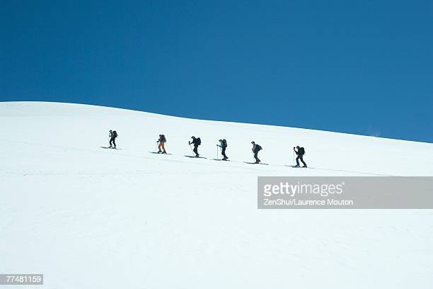 Skiers going up snowy slope, single file