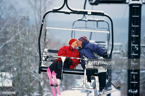 Skiers Kissing on Chair Lift
