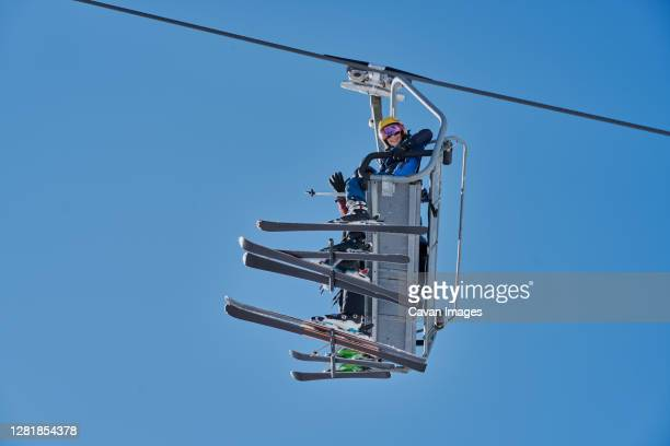 skiers on a chairlift looking down with a blue background - 6 11 months stock pictures, royalty-free photos & images