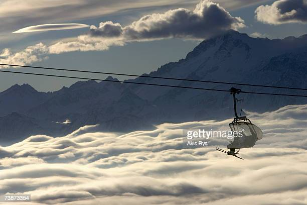skiers on a ski lift ride above the clouds at madonna di campiglio, trentino, italy - マドンナディカンピリオ ストックフォトと画像