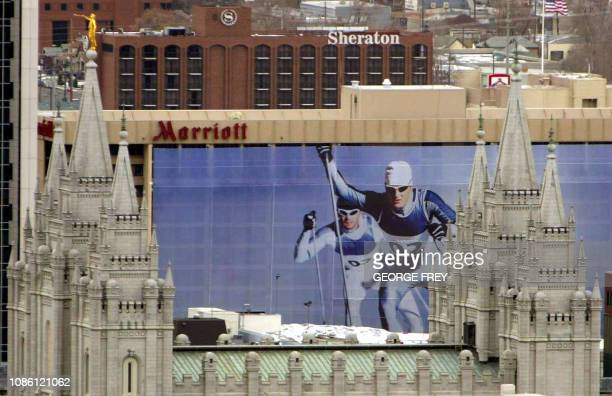 Skiers on an Olympic banner on the side of a building are framed by the spires of the Mormon Temple in downtown Salt Lake City Utah 26 January 2002...