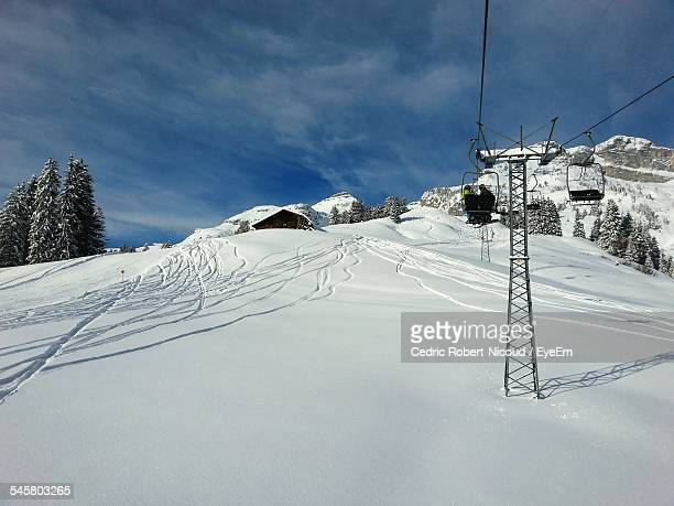skiers on ski lift over snowy mountain - leysin stock photos and pictures