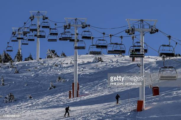 Skiers pass by stopped chairlifts, in Chamrousse, near Grenoble in the Belledone range, on January 7, 2021 as French government's decision to allow...