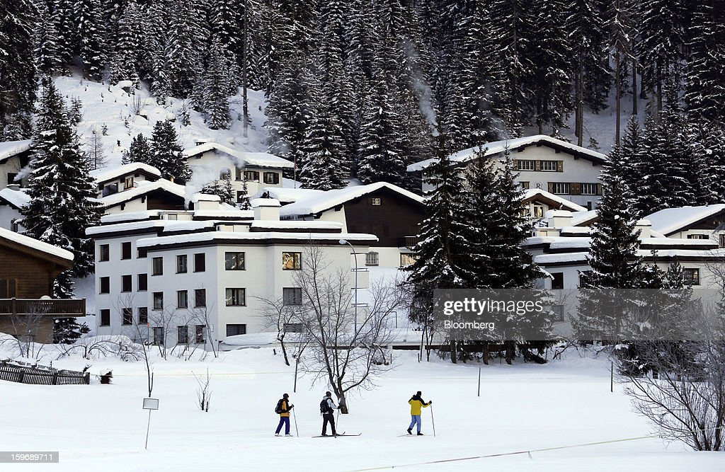 Skiers pass residential homes as they make their way along a track in Davos, Switzerland, on Friday, Jan. 18, 2013. Next week the business elite gather in the Swiss Alps for the 43rd annual meeting of the World Economic Forum in Davos, the five day event runs from Jan. 23-27. Photographer: Chris Ratcliffe/Bloomberg via Getty Images