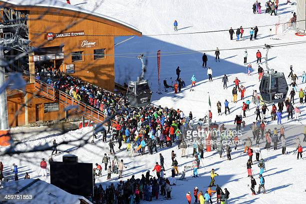Skiers queue up for the cable cars in the French ski resort of Meribel French Alps on December 30 2013 AFP PHOTO / JeanPierre Clatot