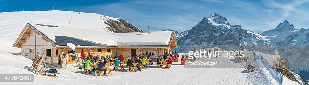 Skiers relaxing at mountain chalet restaurant high in Alps Switzerland