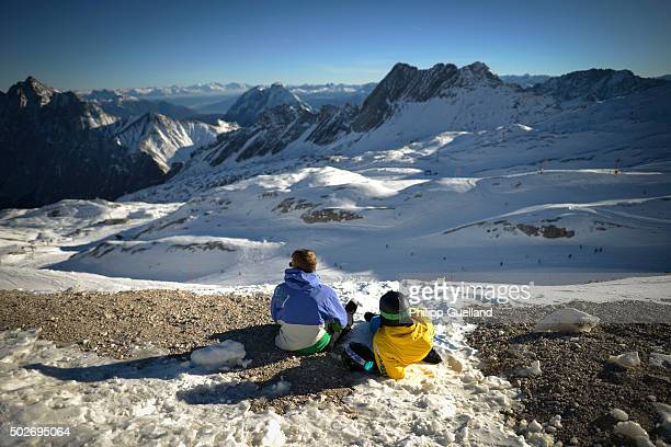 Skiers rest on a patch of snow on a sunny day with temperatures of up to nine degrees Celsius at Zugspitze ski resort in the German Alps on December...